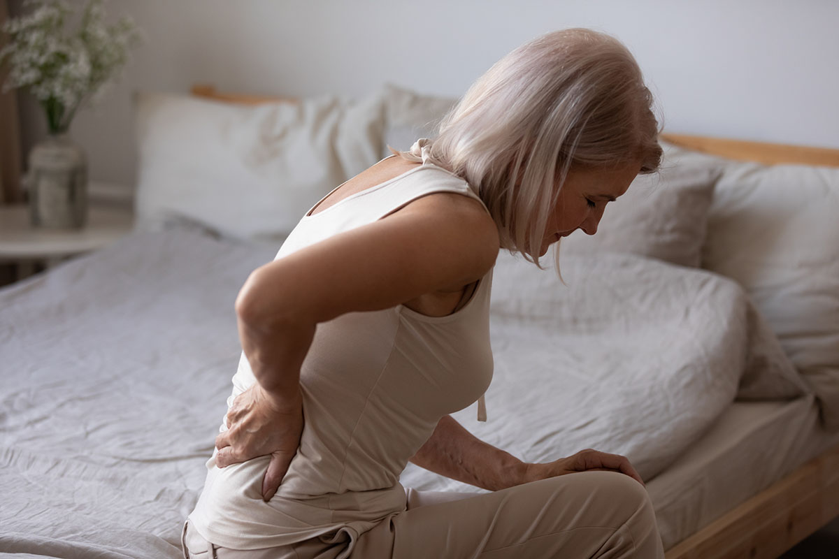 upset mature woman suffering from backache after sleep rubbing stiff-muscles unhappily